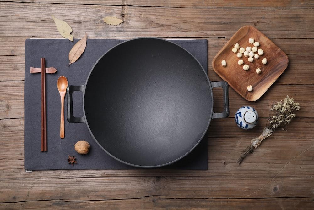 black round plate beside brown wooden scissors