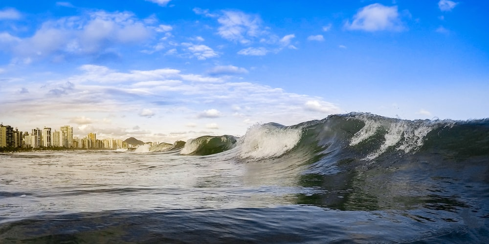 ocean waves crashing on rocks under blue sky and white clouds during daytime