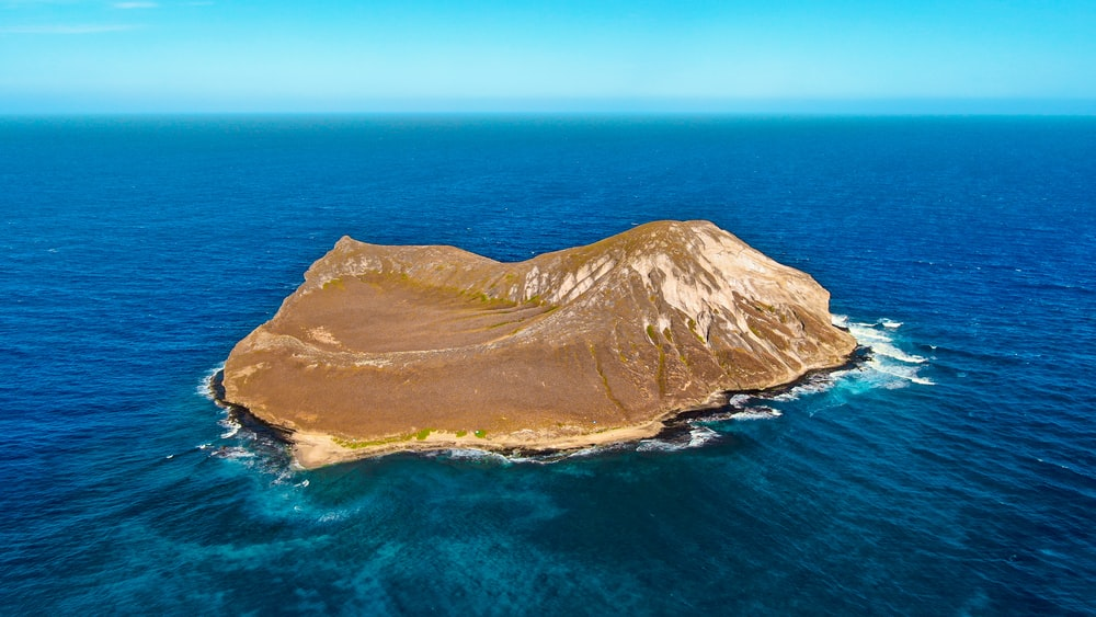 brown mountain beside blue sea during daytime