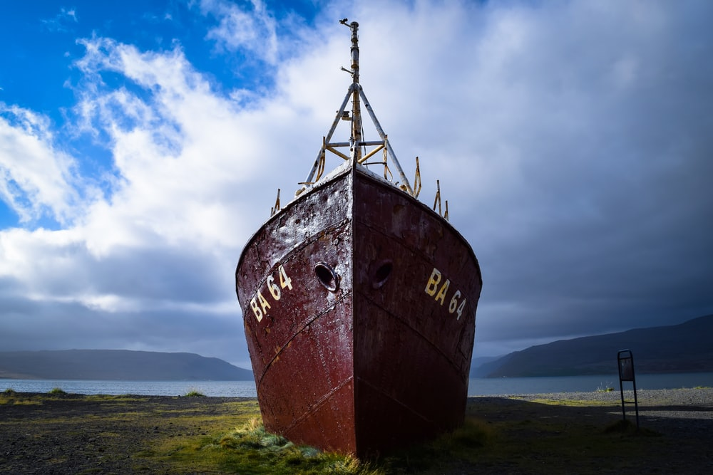 brown ship on green grass field under cloudy sky during daytime