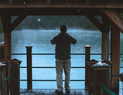 man in black jacket and gray pants standing on brown wooden dock during daytime south carolina zoom background