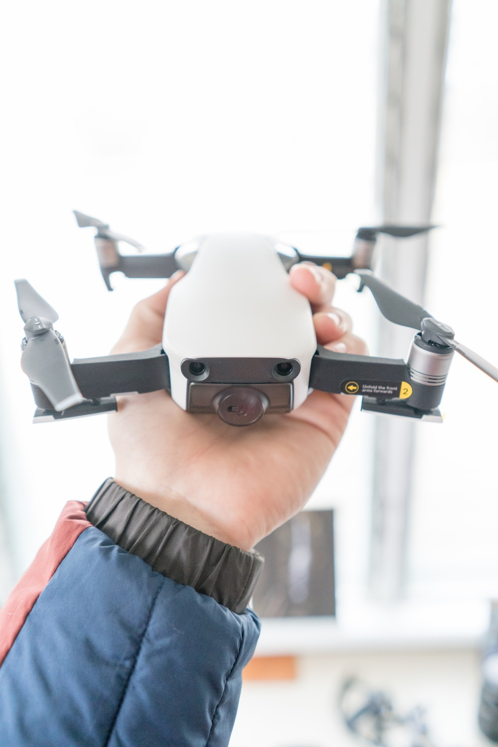person in brown shirt holding gray and black drone