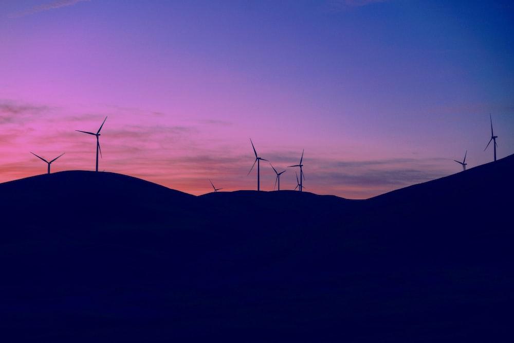 wind turbines on hill during dusk