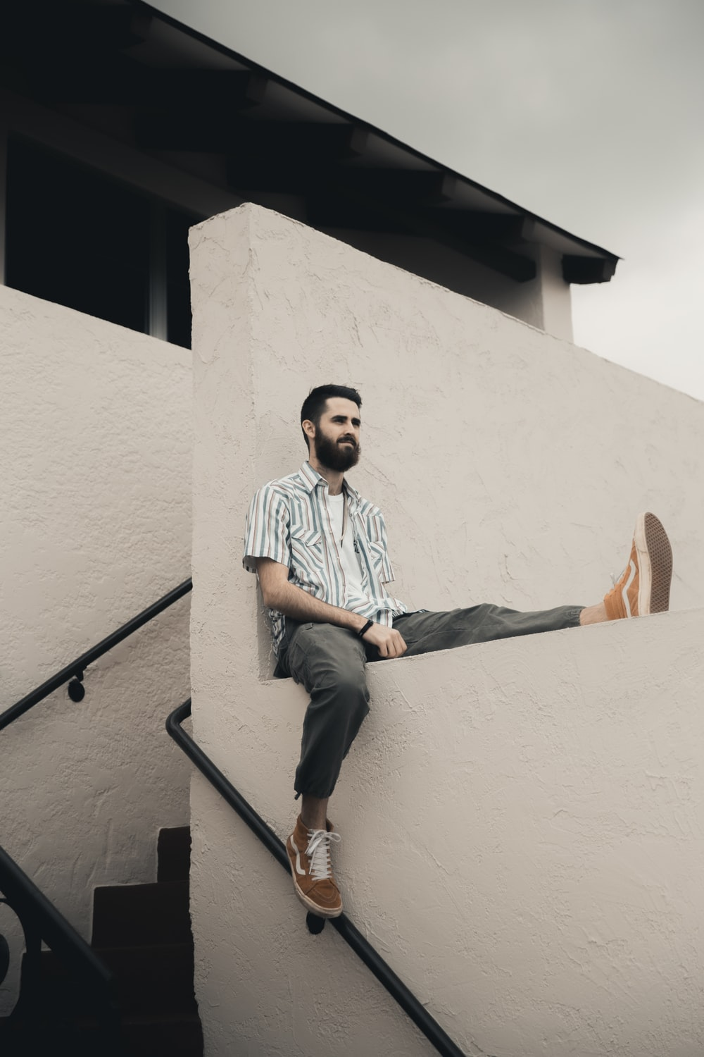 man in blue and white stripe dress shirt and blue denim jeans sitting on concrete staircase