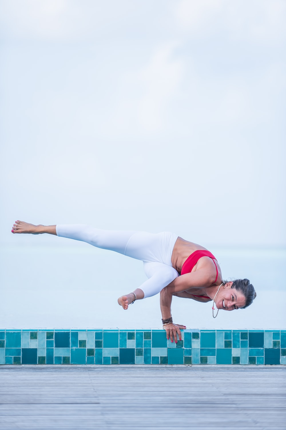 woman in white tank top and white pants doing yoga