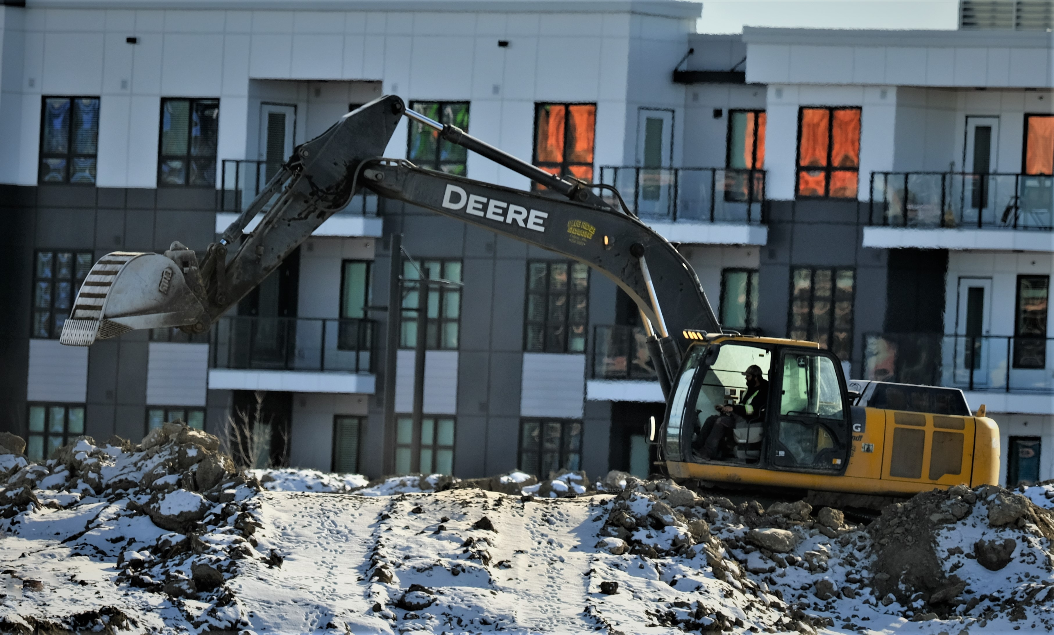 yellow and black excavator on snow covered ground near building during daytime