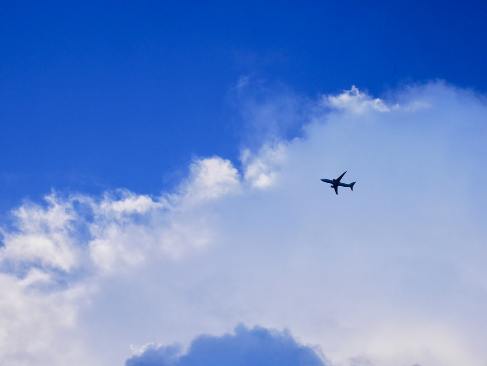 black airplane flying in the sky during daytime