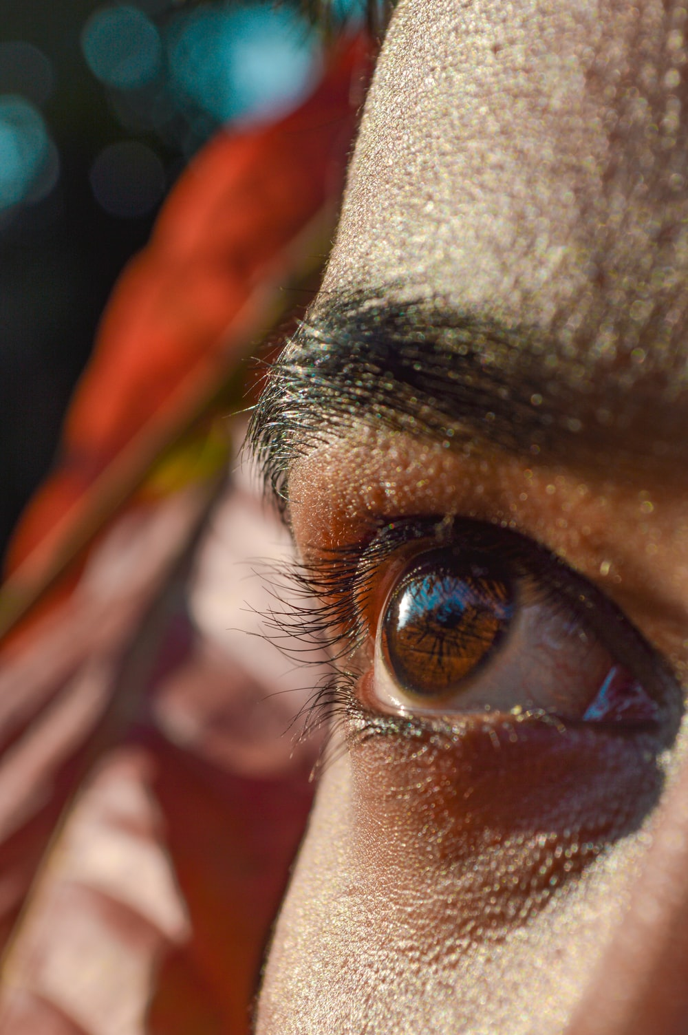 persons eye with orange and yellow feather