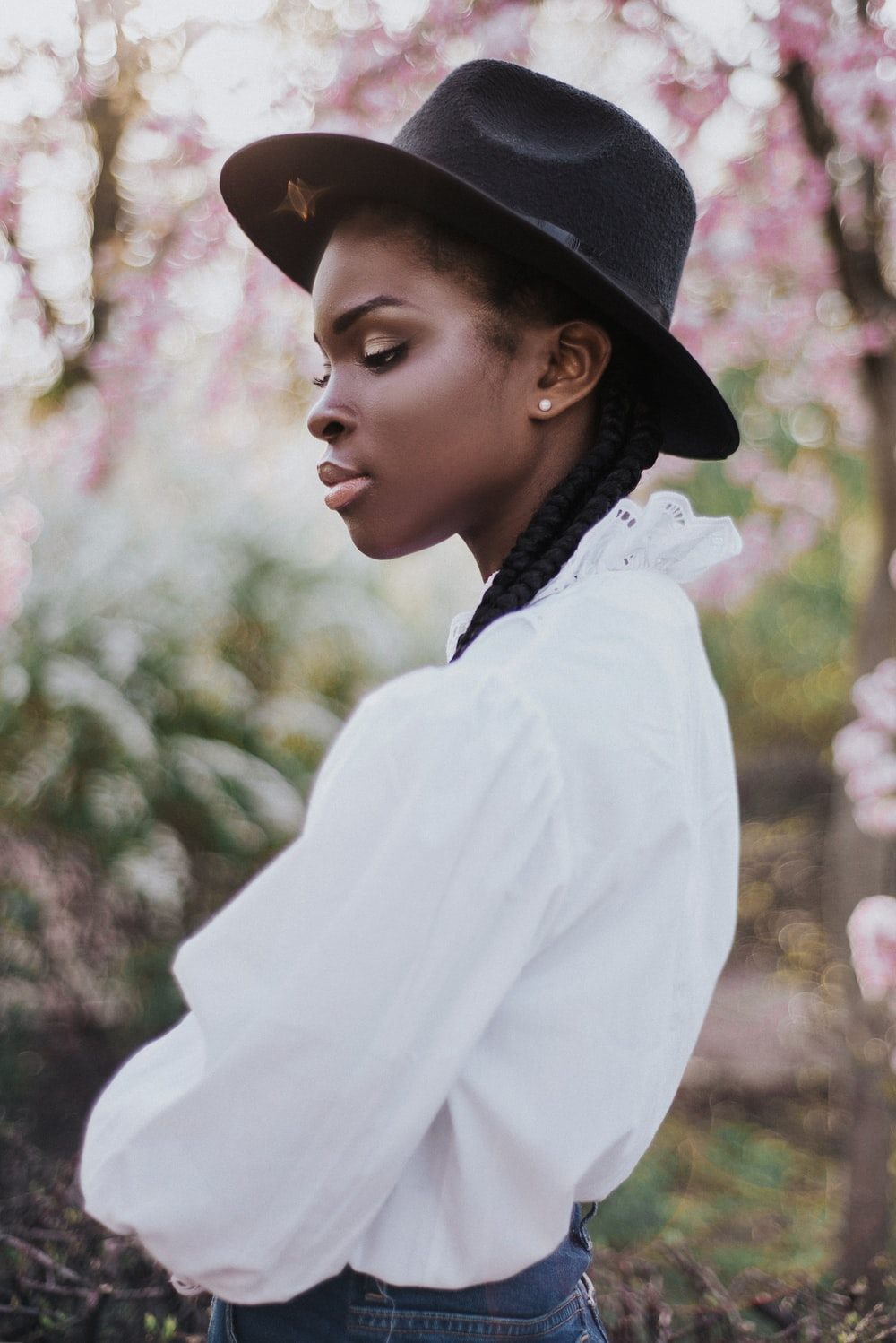 woman in white long sleeve shirt and black hat
