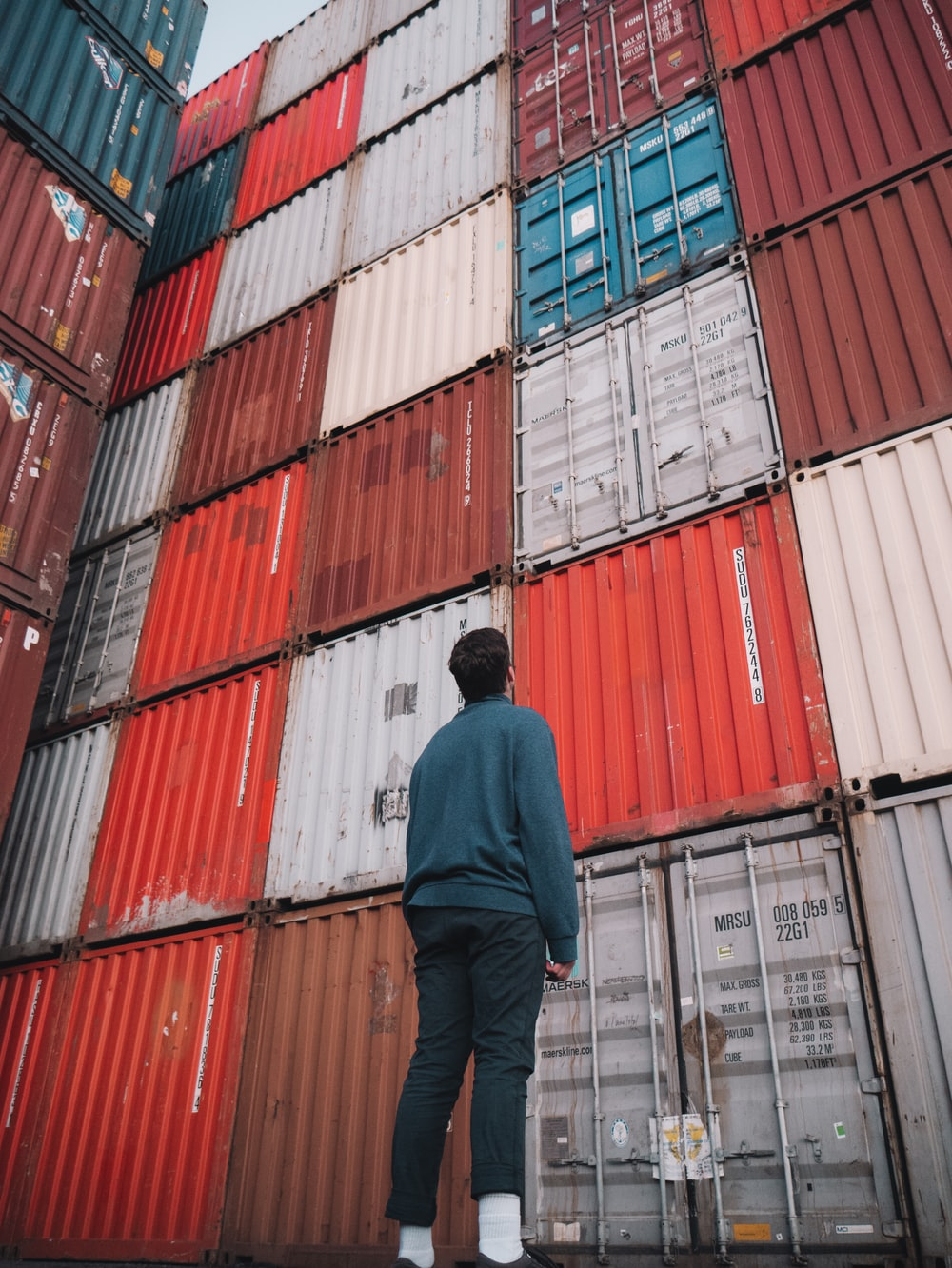 man in black jacket standing in front of red and blue intermodal containers