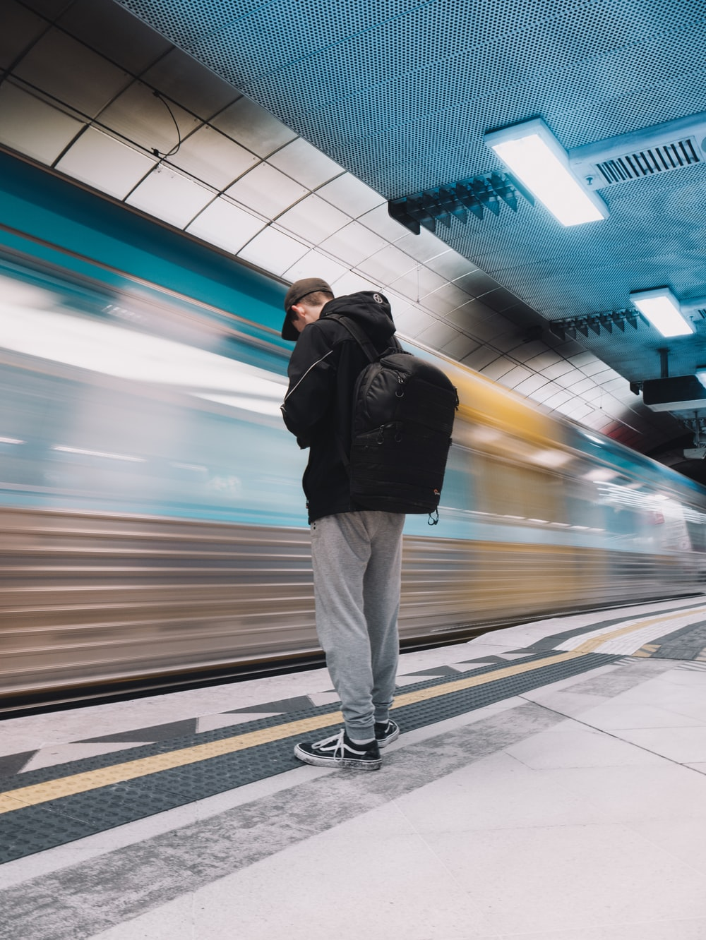 man in black jacket and white pants standing on train station
