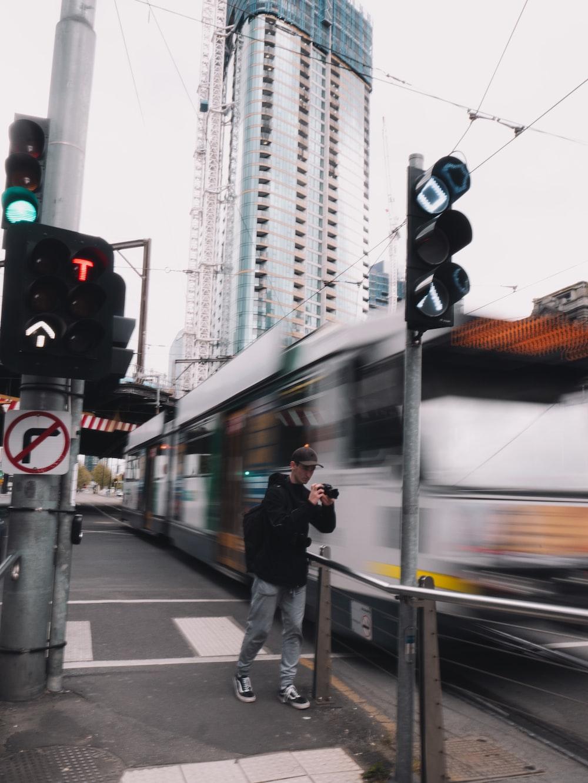 man in black jacket standing beside traffic light during daytime
