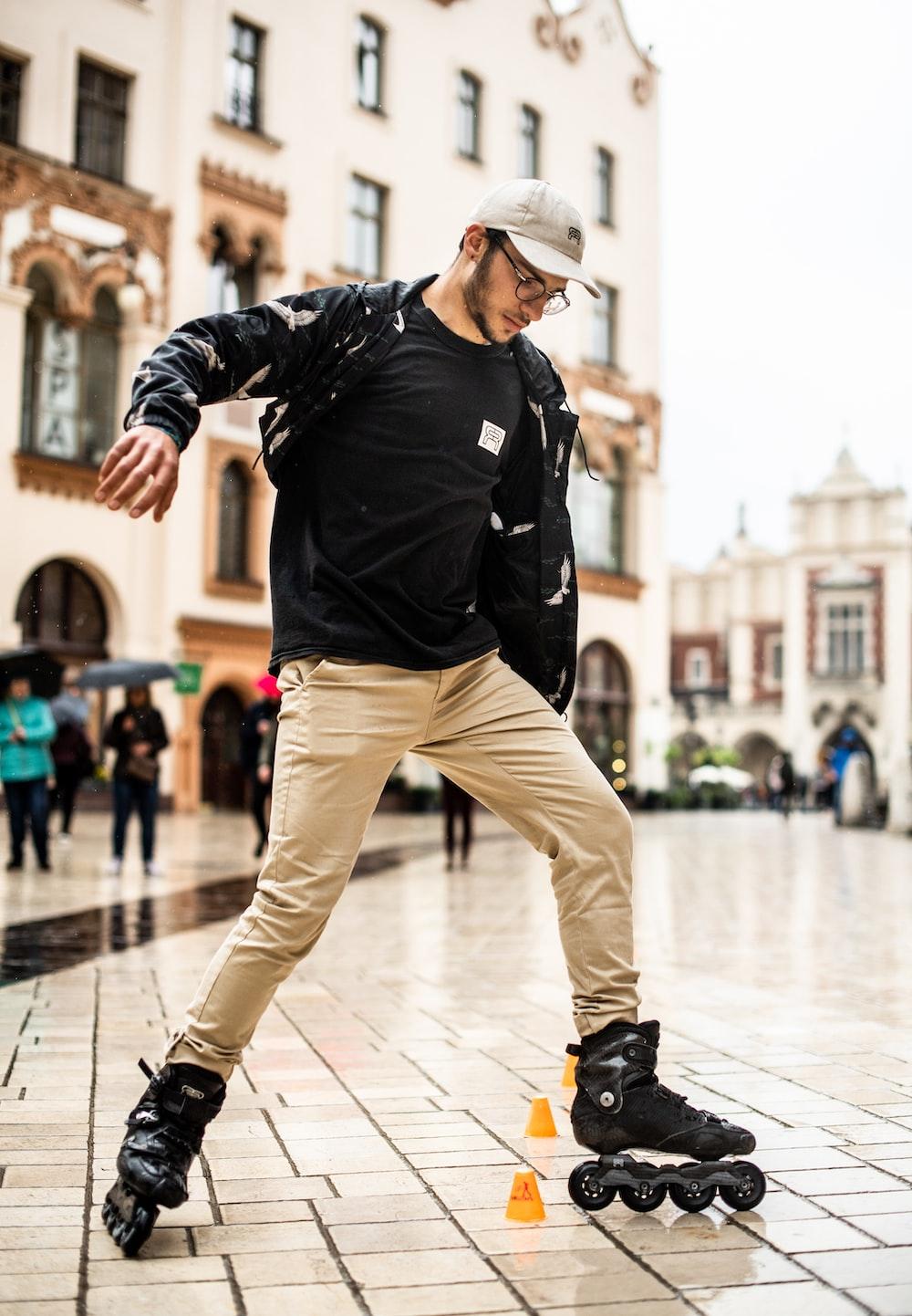 man in black jacket and brown pants wearing brown cowboy hat walking on white floor tiles