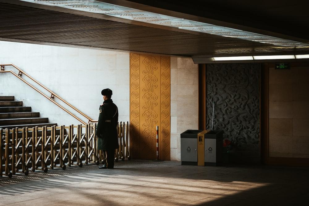man in black jacket and pants standing on brown wooden floor