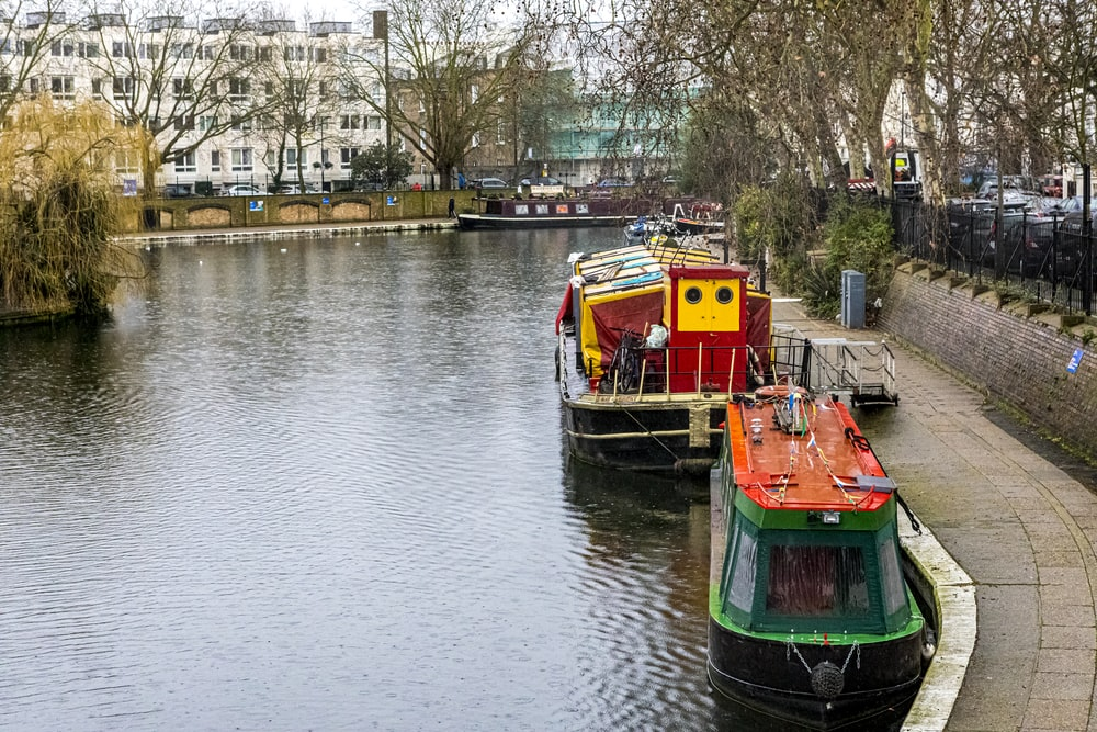 green and orange boat on river during daytime