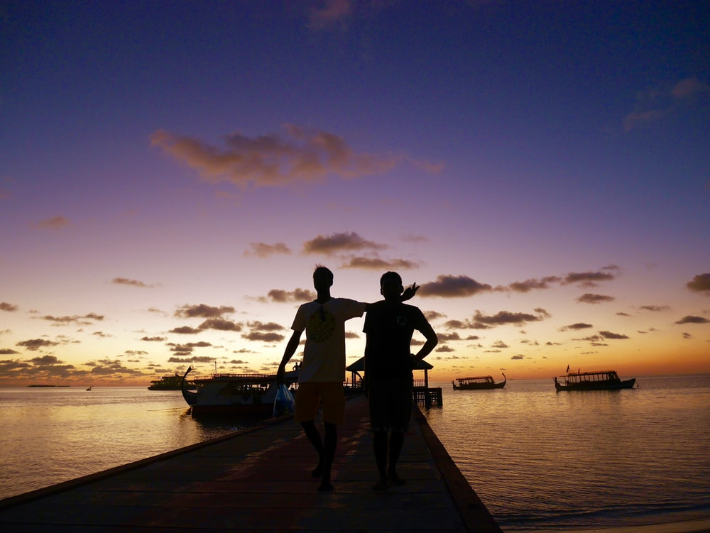 couple standing on wooden dock during sunset