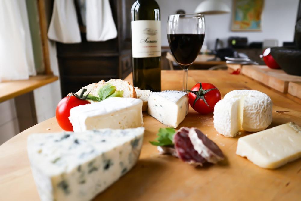 sliced cheese on bread beside wine bottle