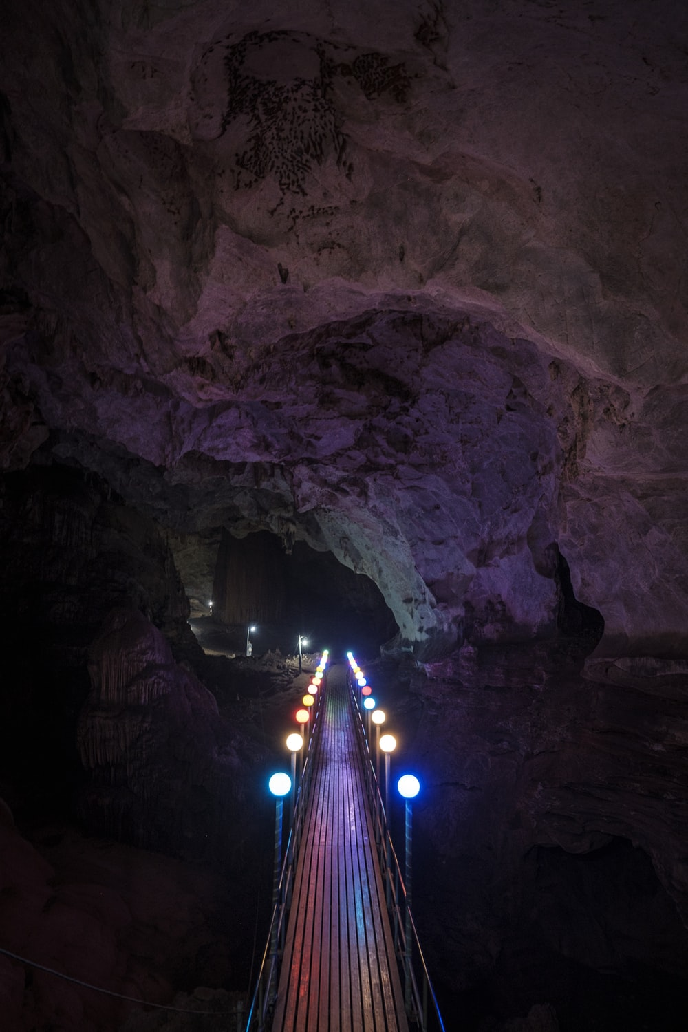 lighted bridge in cave during night time