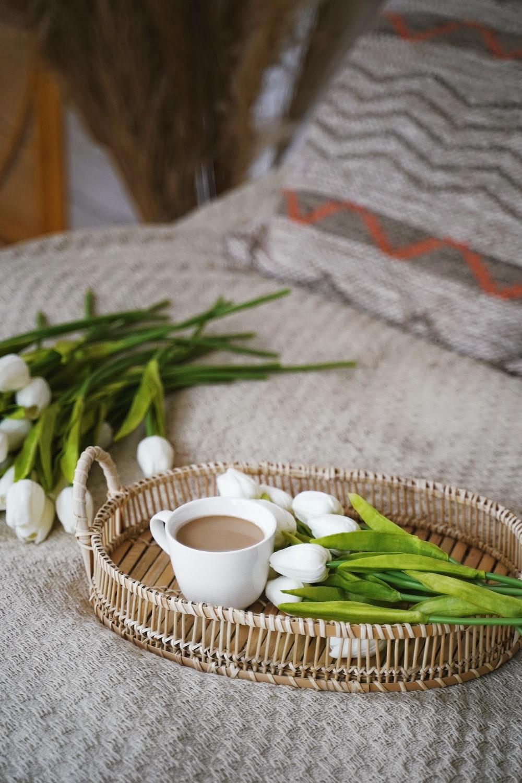 white ceramic mug on brown woven basket