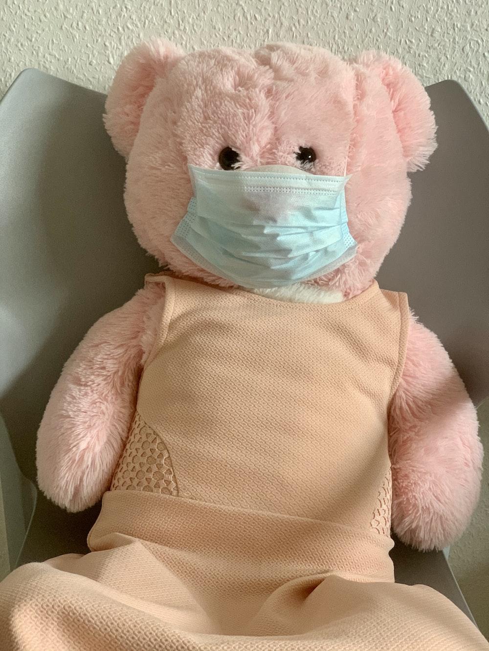 pink bear plush toy on white textile