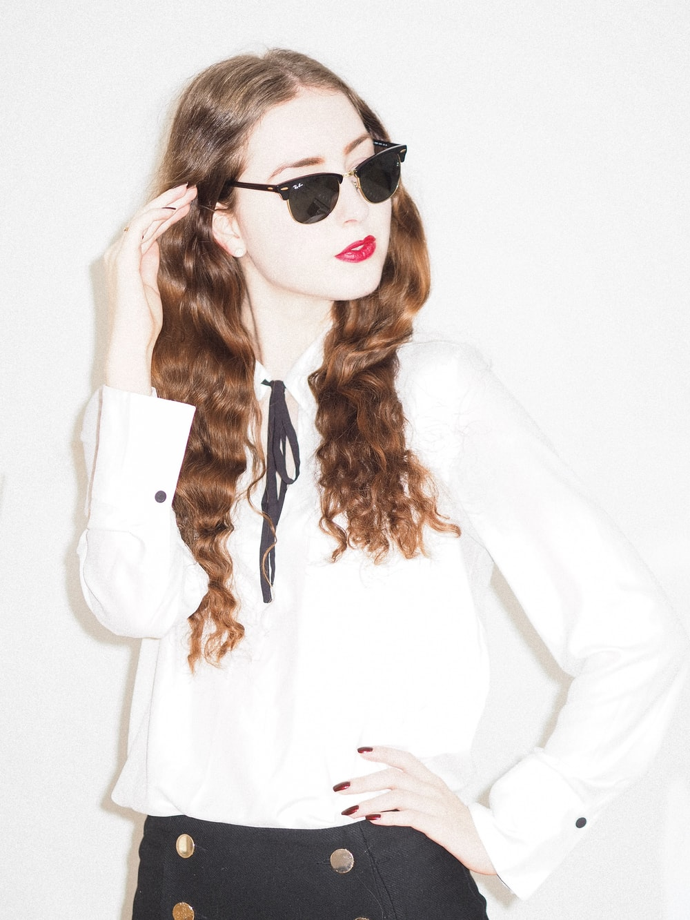 woman in white long sleeve shirt wearing black sunglasses