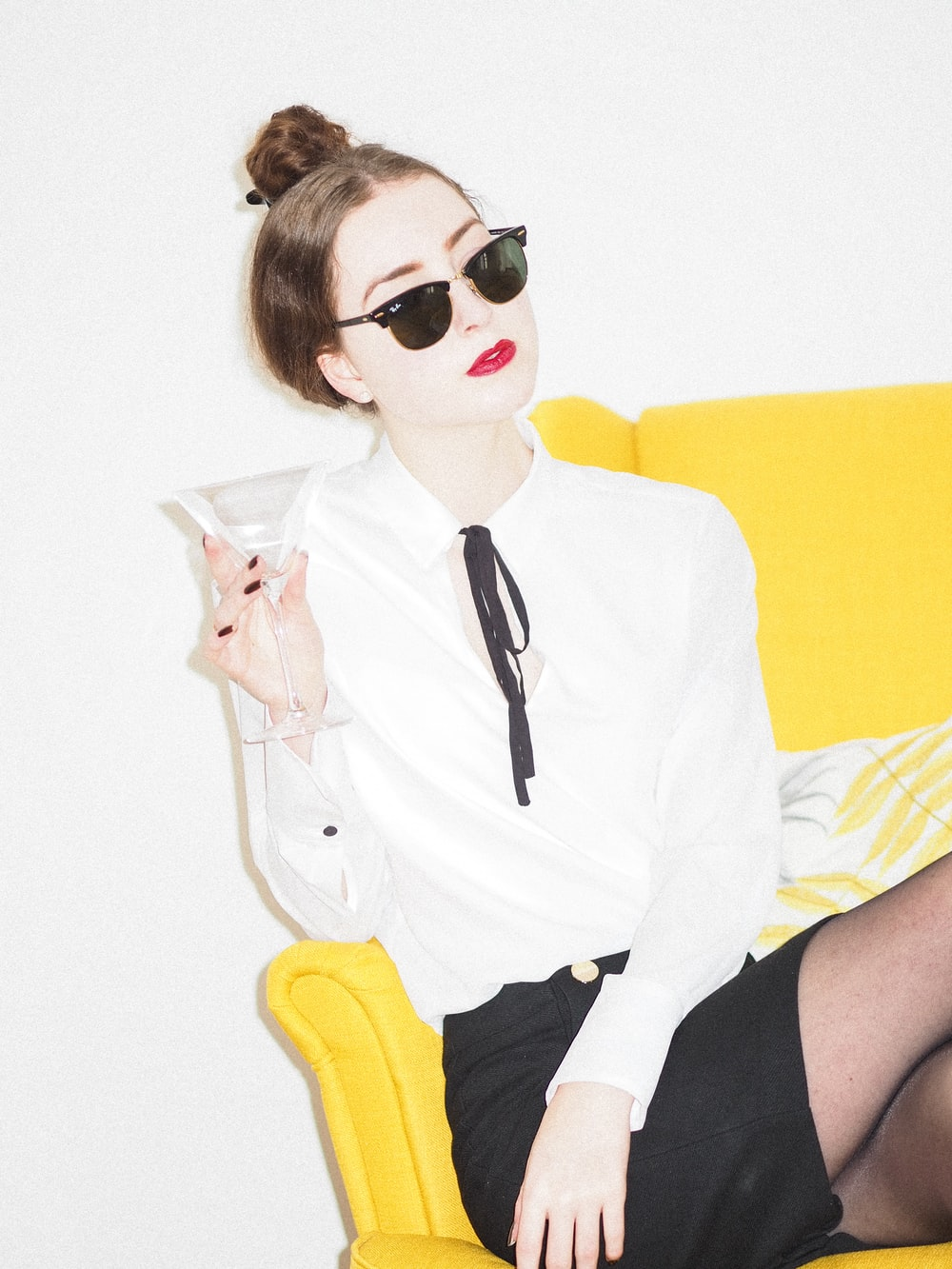 woman in white dress shirt and black skirt sitting on yellow couch