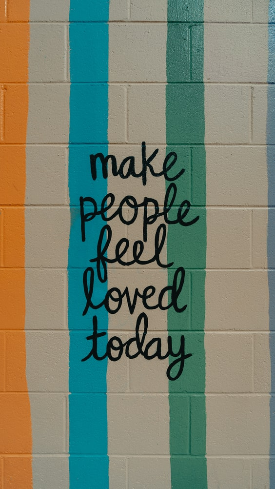 "A photo of a white brick wall. There are coloured stripes in yellow, blue and green, and over it is painted in cursive, ""make people feel loved today."""