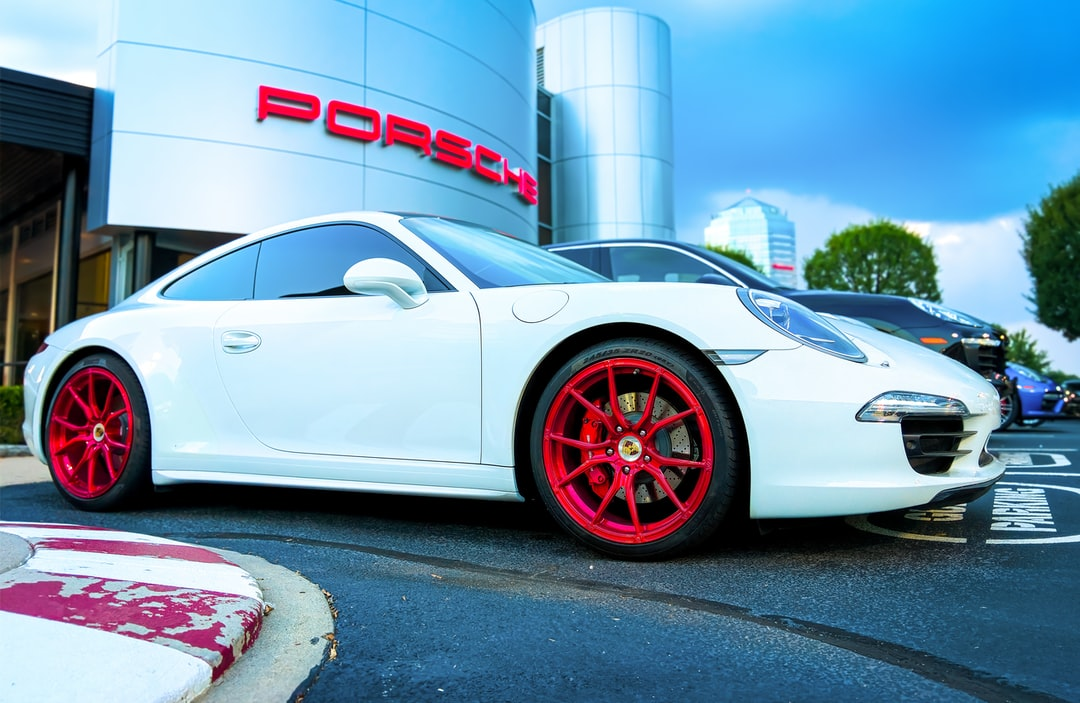 White Porsche with blood red rims parked in front of the Showroom Marquee in Tyson's Corner Virginia on a cloudy day.