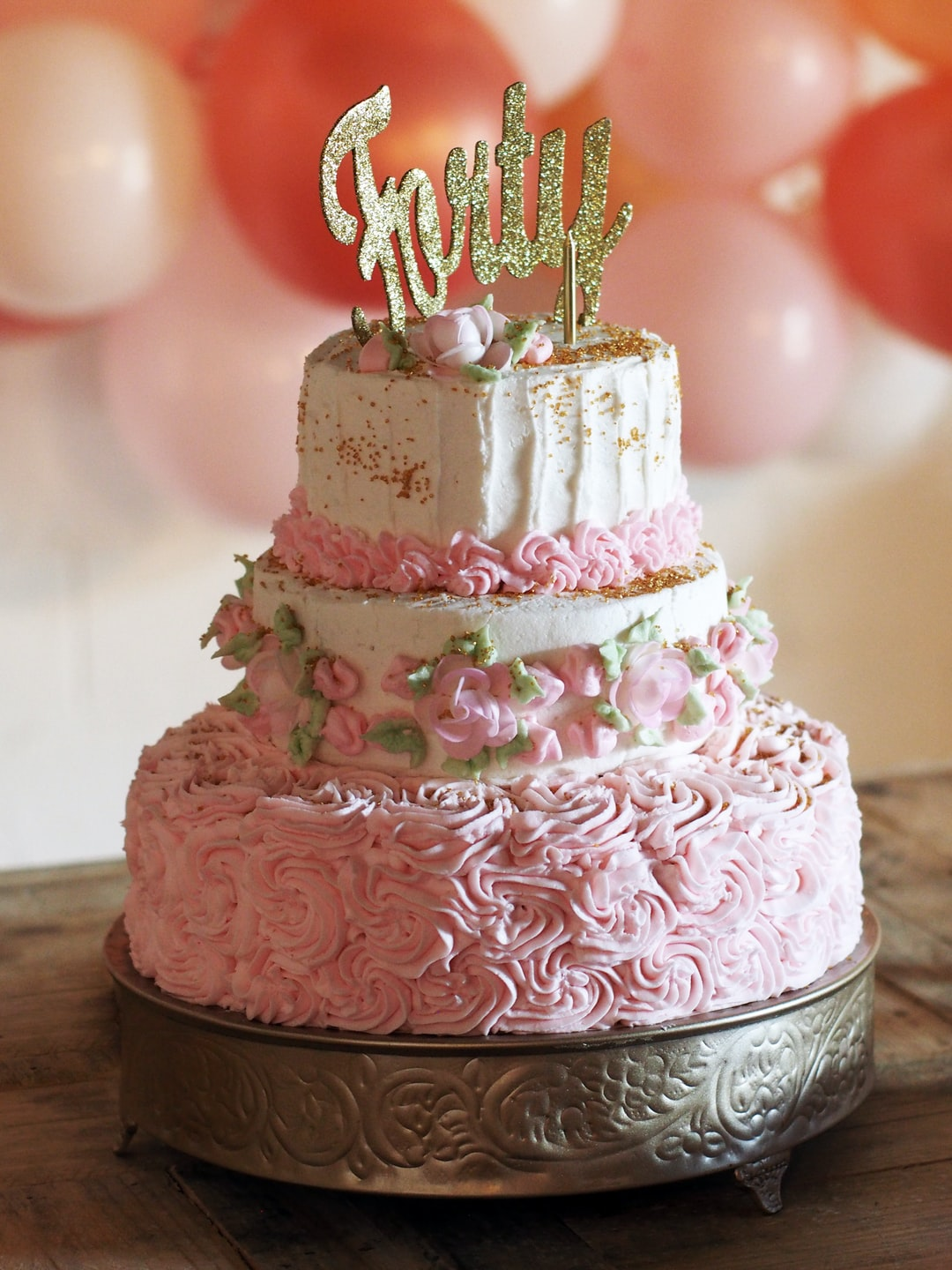 Pink birthday cake with roses and balloons to celebrate forty