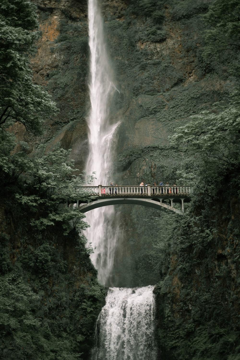 green bridge over waterfalls during daytime