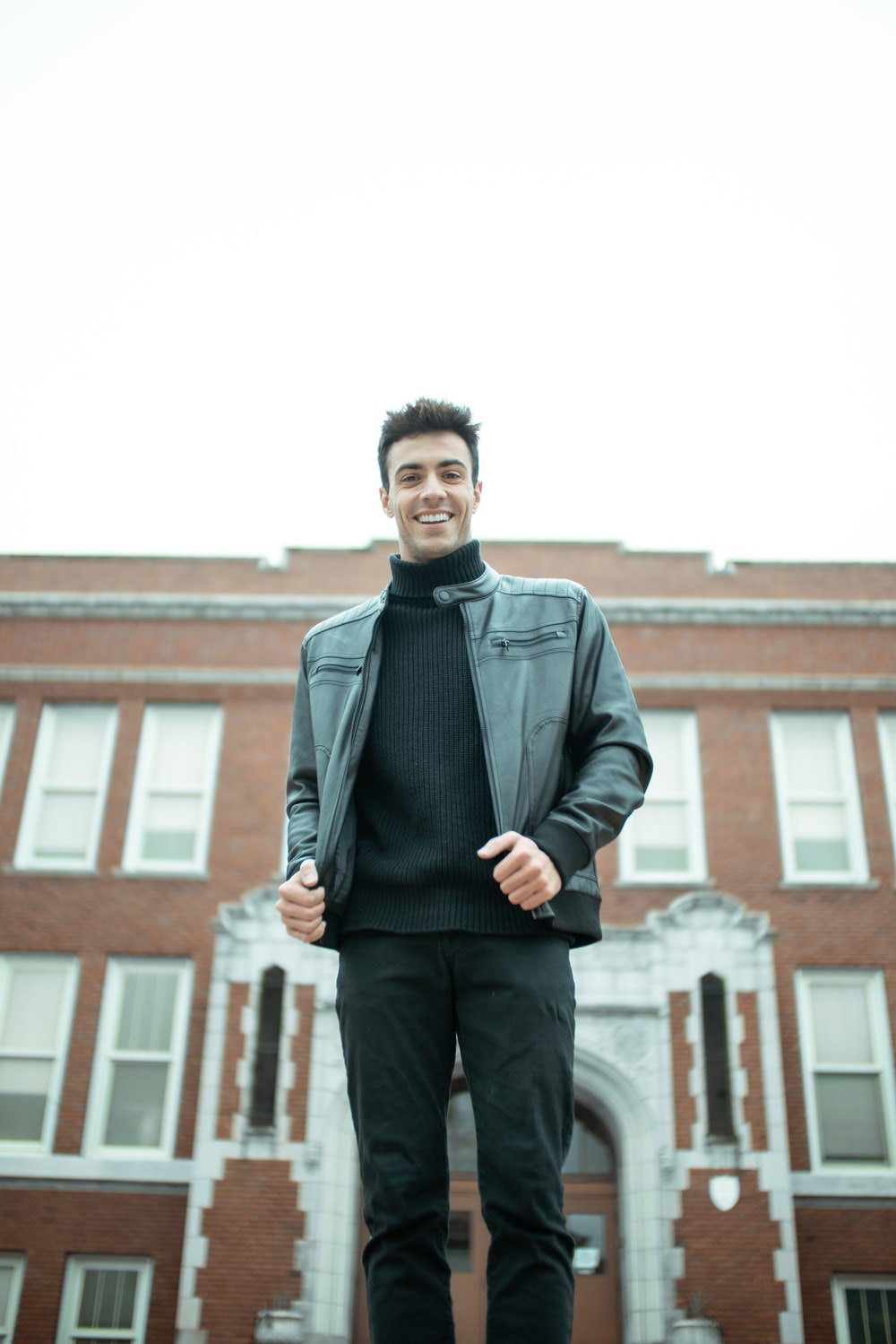 man in black leather jacket standing near brown concrete building during daytime