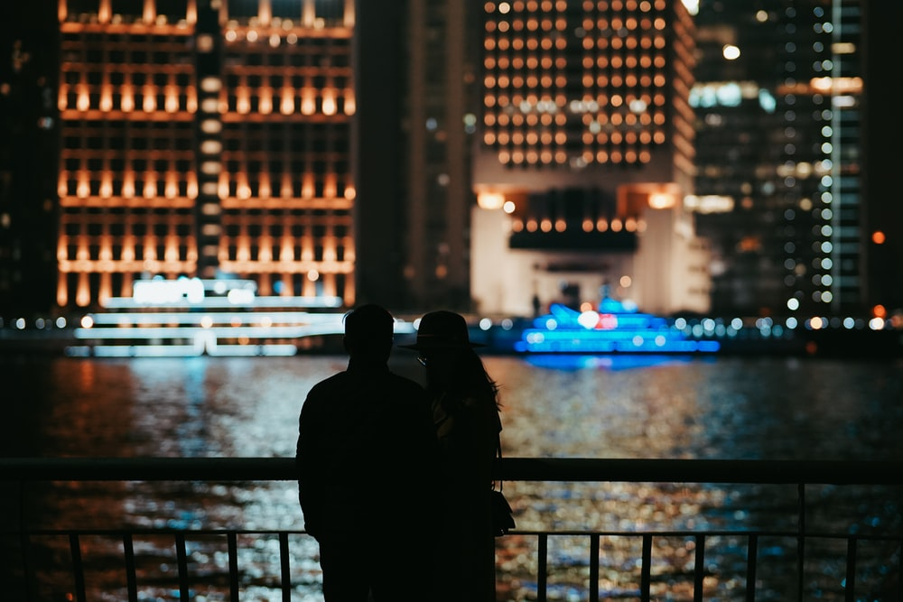 silhouette of person standing near railings during night time