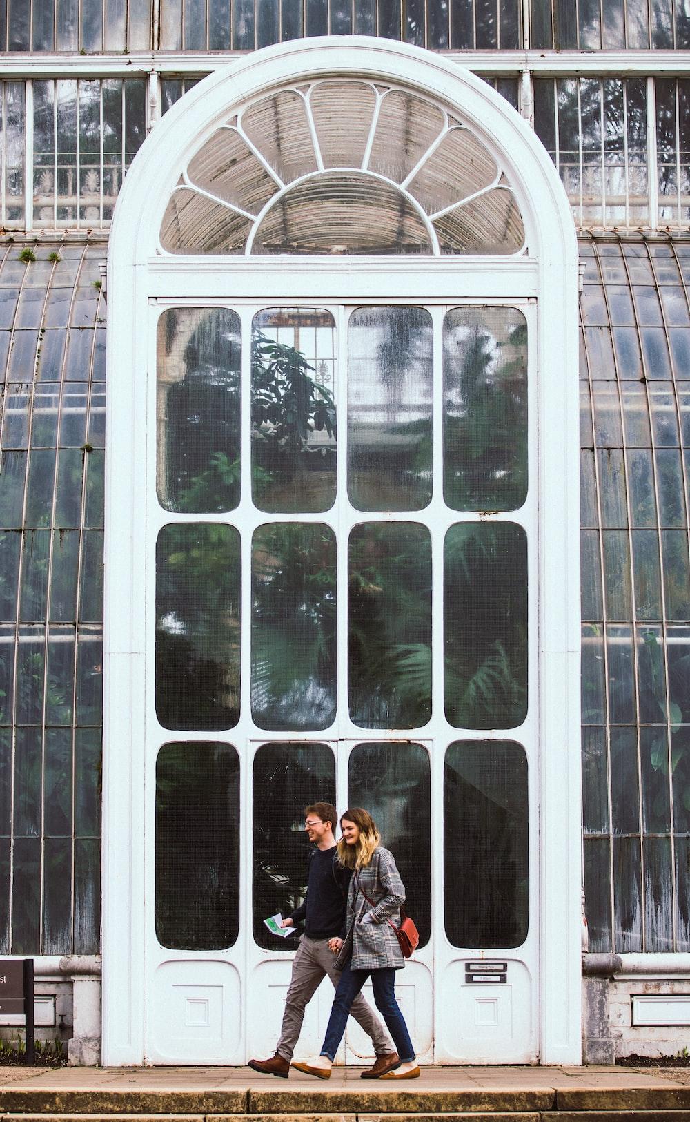 woman in black jacket standing beside glass window