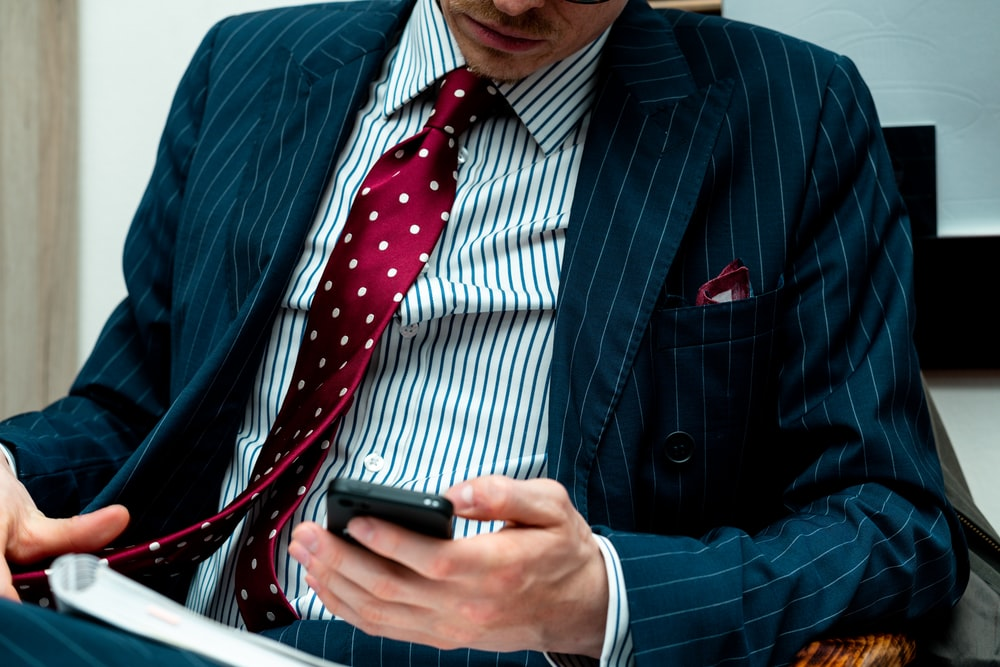 man in blue suit jacket holding black smartphone