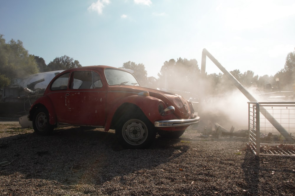 red and white vintage car on brown soil
