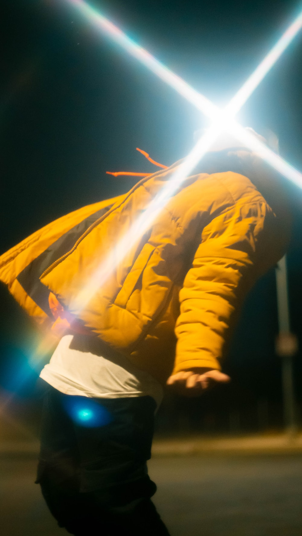 man in yellow jacket holding blue light