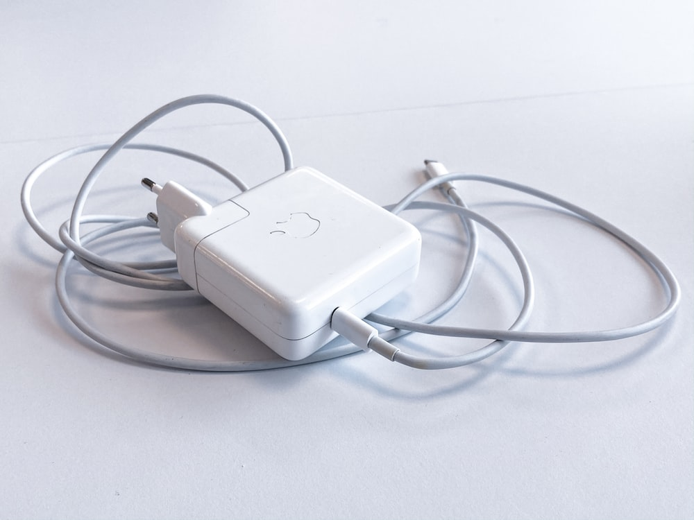 white apple charging adapter on white table