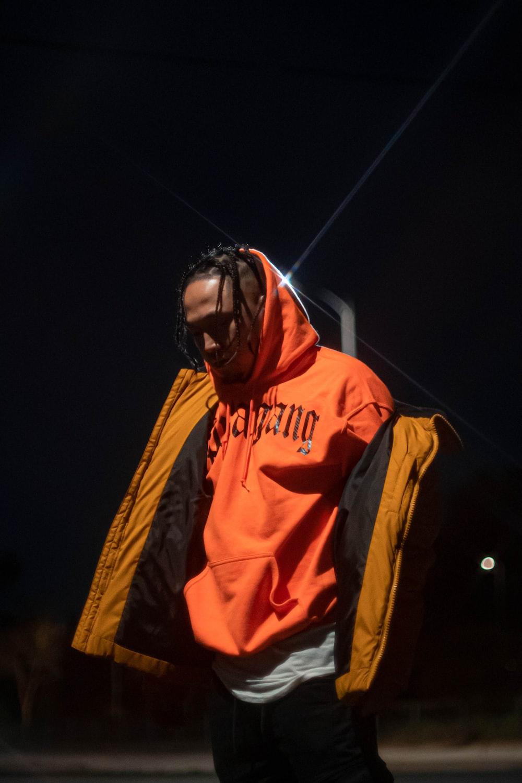 man in orange hoodie wearing black sunglasses