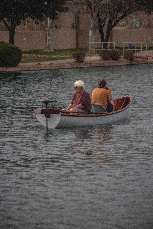 2 men riding on boat during daytime
