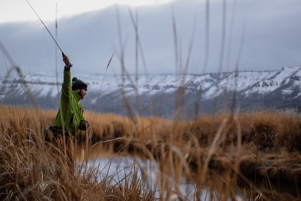 man in green jacket and black pants holding fishing rod standing on brown grass field during