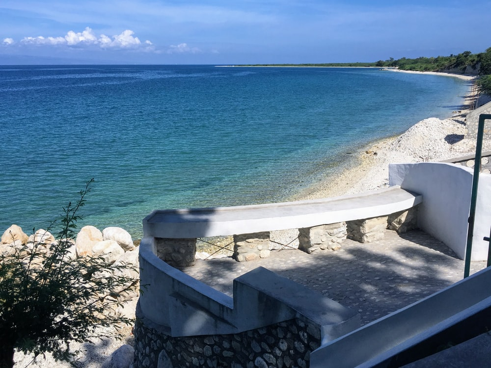 white concrete bench near blue sea under blue sky during daytime