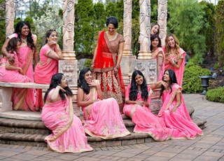 group of women in red and gold sari dress sitting on brown wooden bench