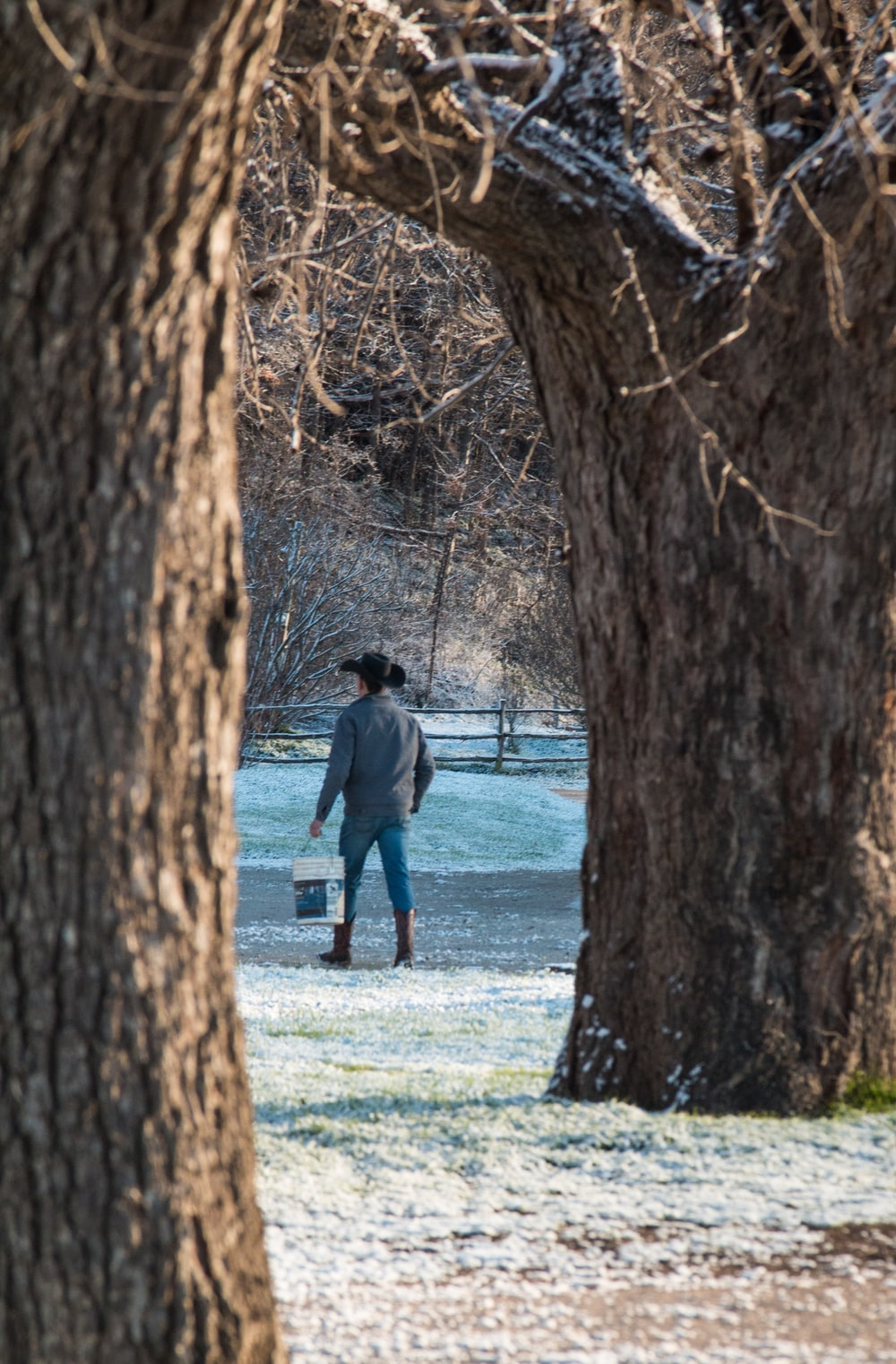 man and woman walking on green grass field near body of water during daytime