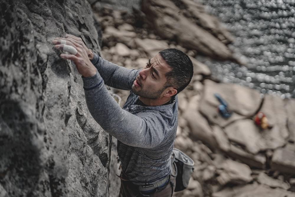 man in grey long sleeve shirt climbing on rock