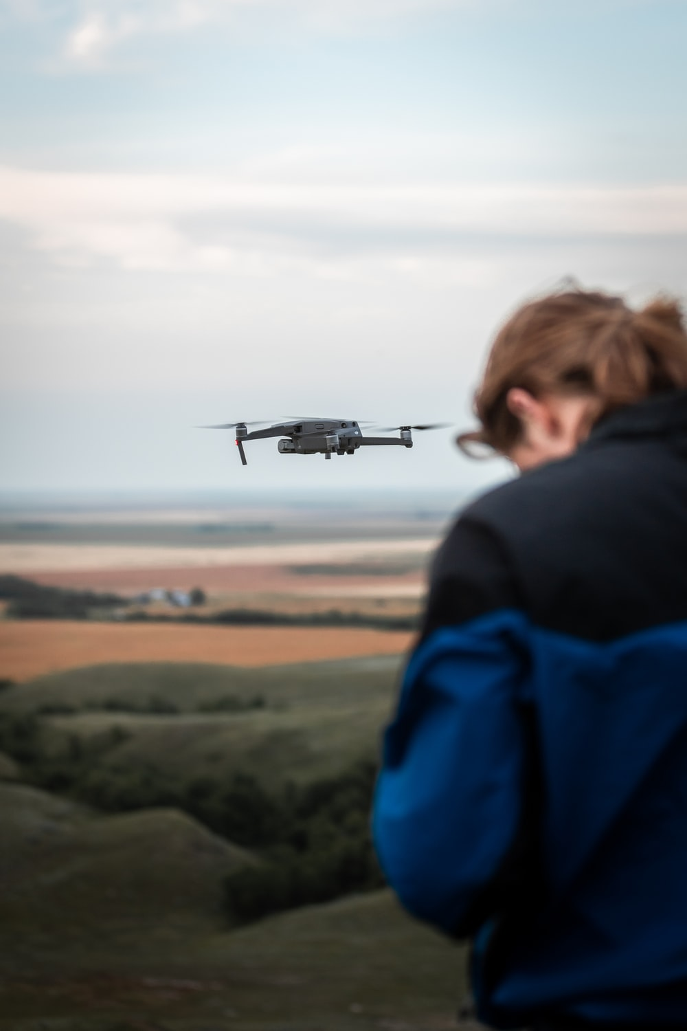 man in blue jacket looking at gray drone