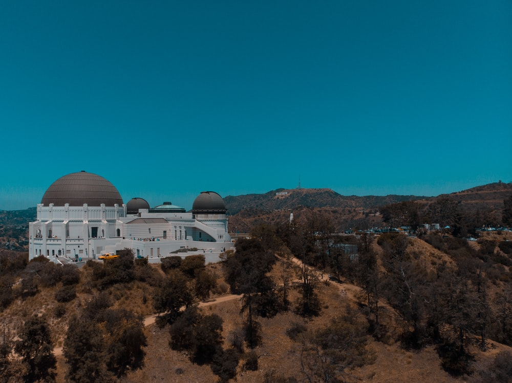 white dome building on brown and green mountain under blue sky during daytime