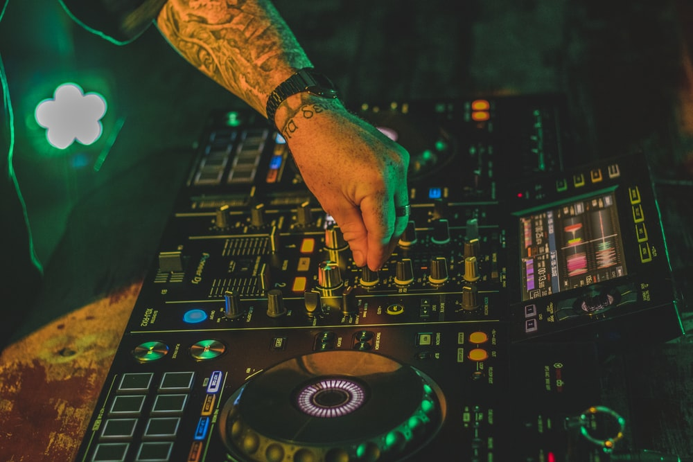 person playing dj mixer with green lights