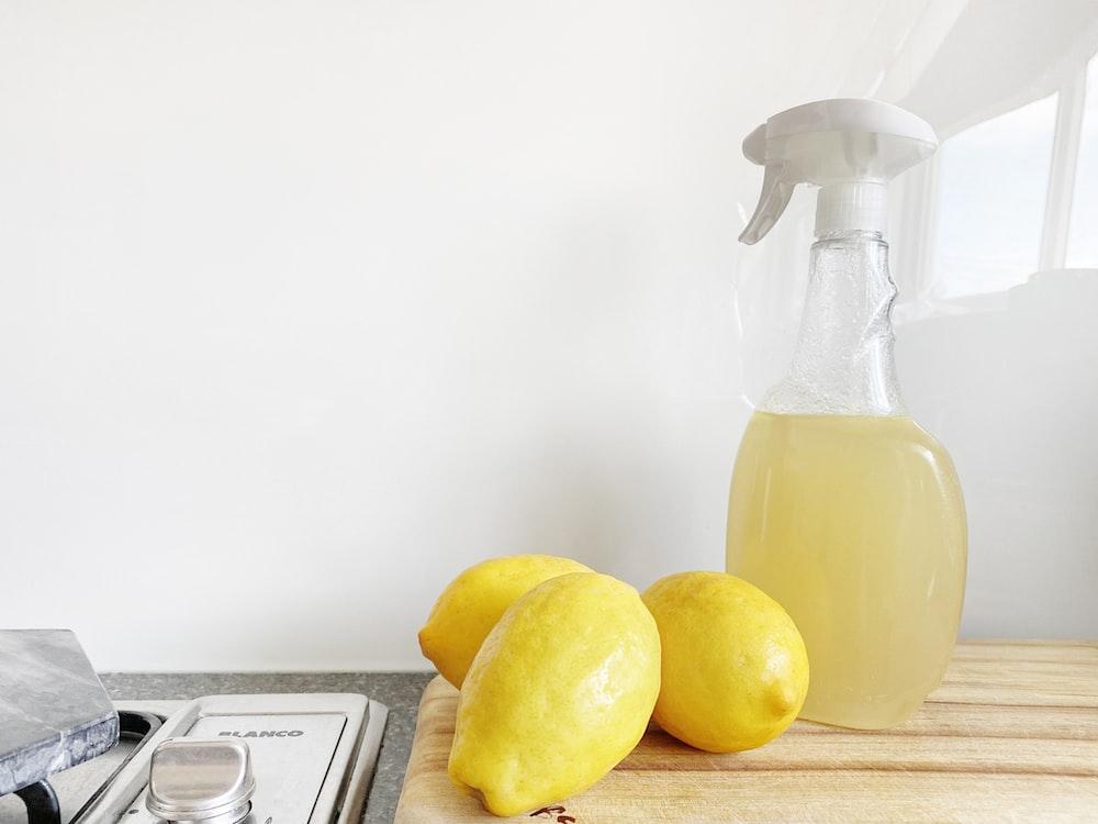 yellow lemon fruit beside clear glass bottle