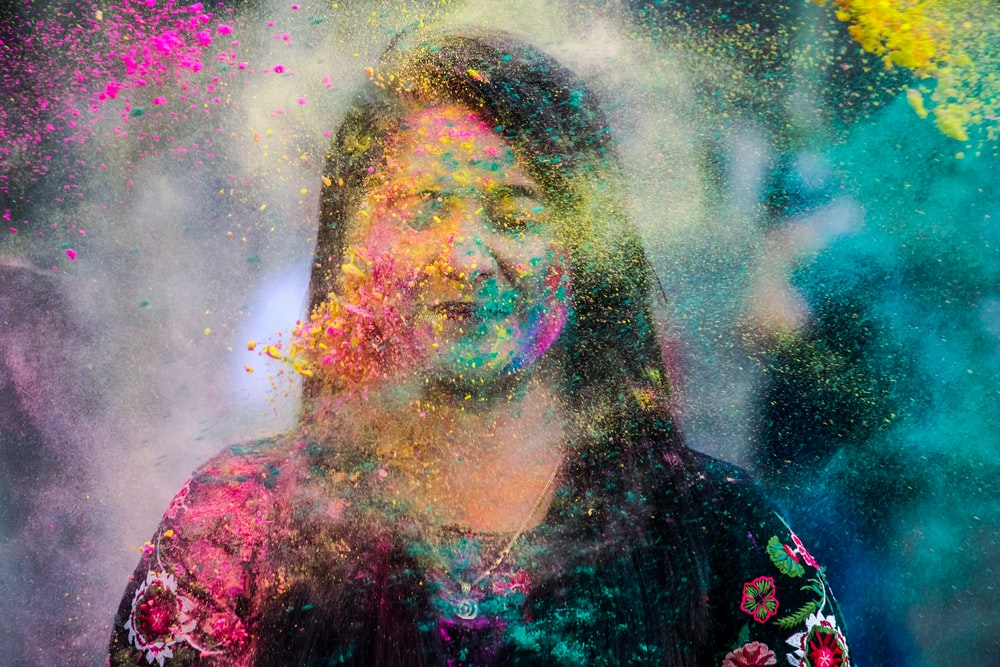 woman in black and red floral shirt with yellow and green powder on her face