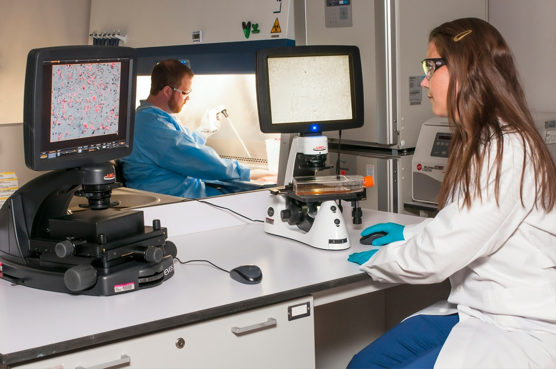 A technician viewing a blot on a fluorescence microscope while another technician is using a pipette at the Advanced Technology Research Facility (ATRF), Frederick National Laboratory for Cancer Research, National Cancer Institute.